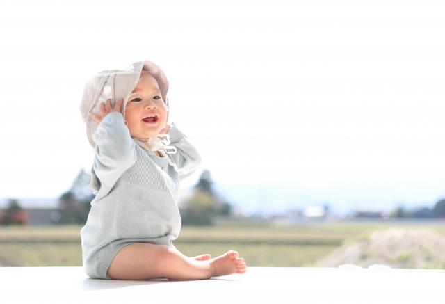 陽だまりの中ほほえむ赤ちゃんの写真